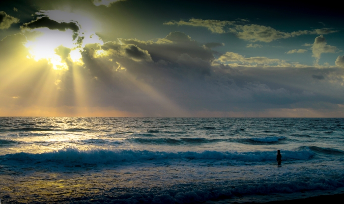 Here is a shot I took while in Florida.  I loved the perspective of how small the person is compared to  the majesty of the ocean and the suns rays washing out the entire scene.